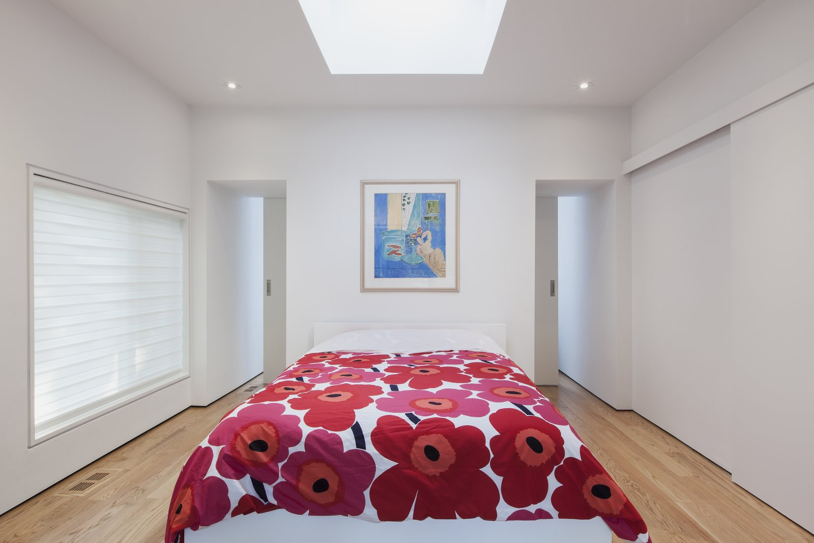 From the top of the staircase, the master bedroom is accessed via sliding doors (on the right), while a pair of pocket doors lead to a walk-in closet that overlooks the living room. A skylight with an operable shade provides natural light when desired.