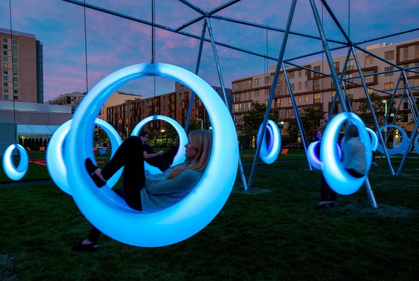 An installation brought 20 circular, glowing swings to a grassy area near the Boston Convention Center. LED lights embedded in the polypropylene swings change color depending on its motion.