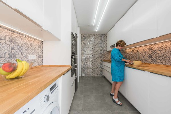 Though much of the apartment favors a minimal, white palette, the kitchen embraces pattern and texture through the warm wood counters and traditional ceramic tiling.