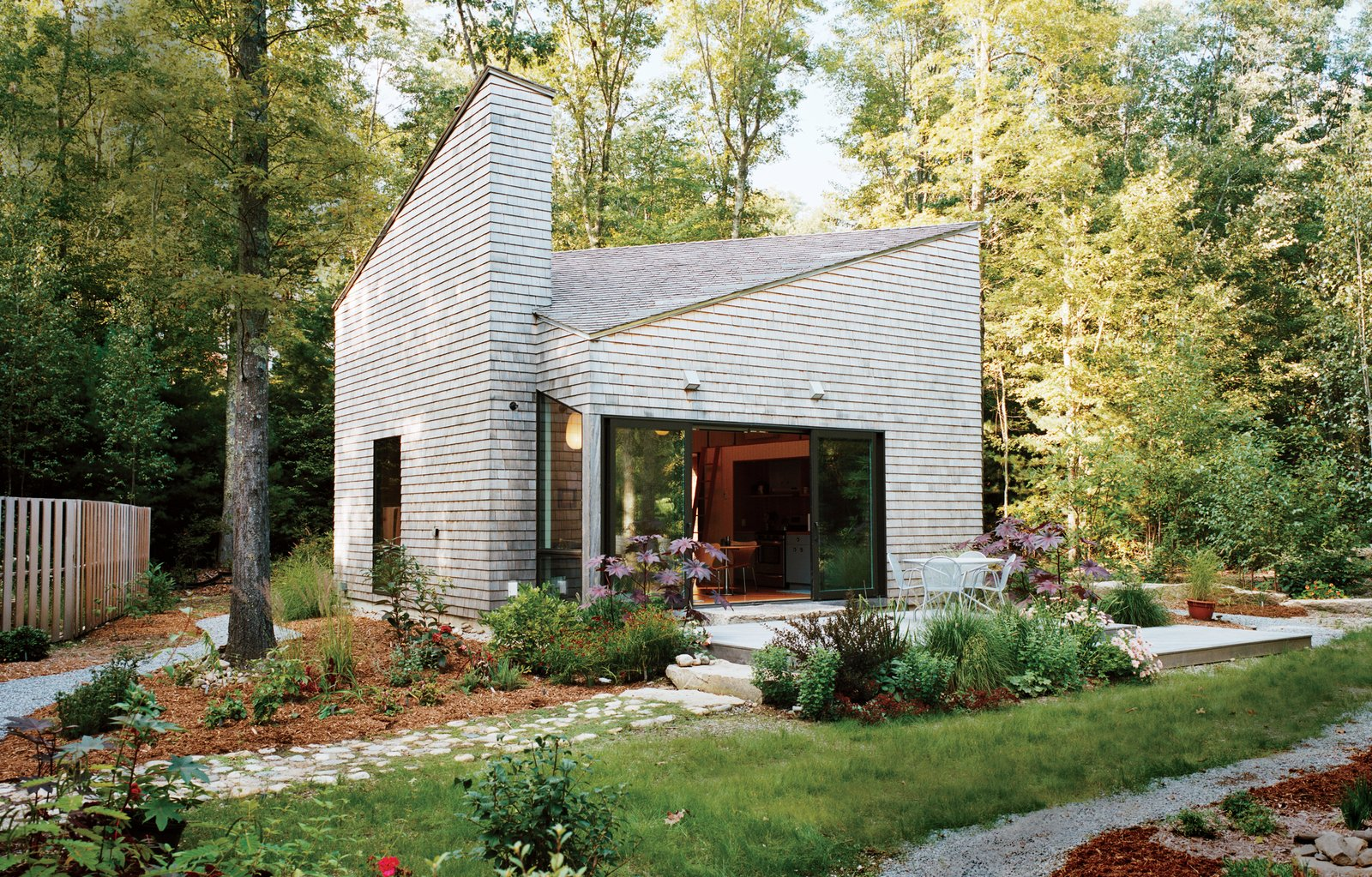 An artist by trade, and gardener by passion, Allison Paschke commissioned Providence-based architecture firm 3SIXØ to build a modest cottage that would allow her to reconnect with nature. She landscaped the home's lush gardens herself. Tagged: Exterior, Tiny Home Building Type, Wood Siding Material, and Shingles Roof Material.  Photo 1 of 12 in This Tiny New England Cottage Is a No-Frills Weekend Hideaway