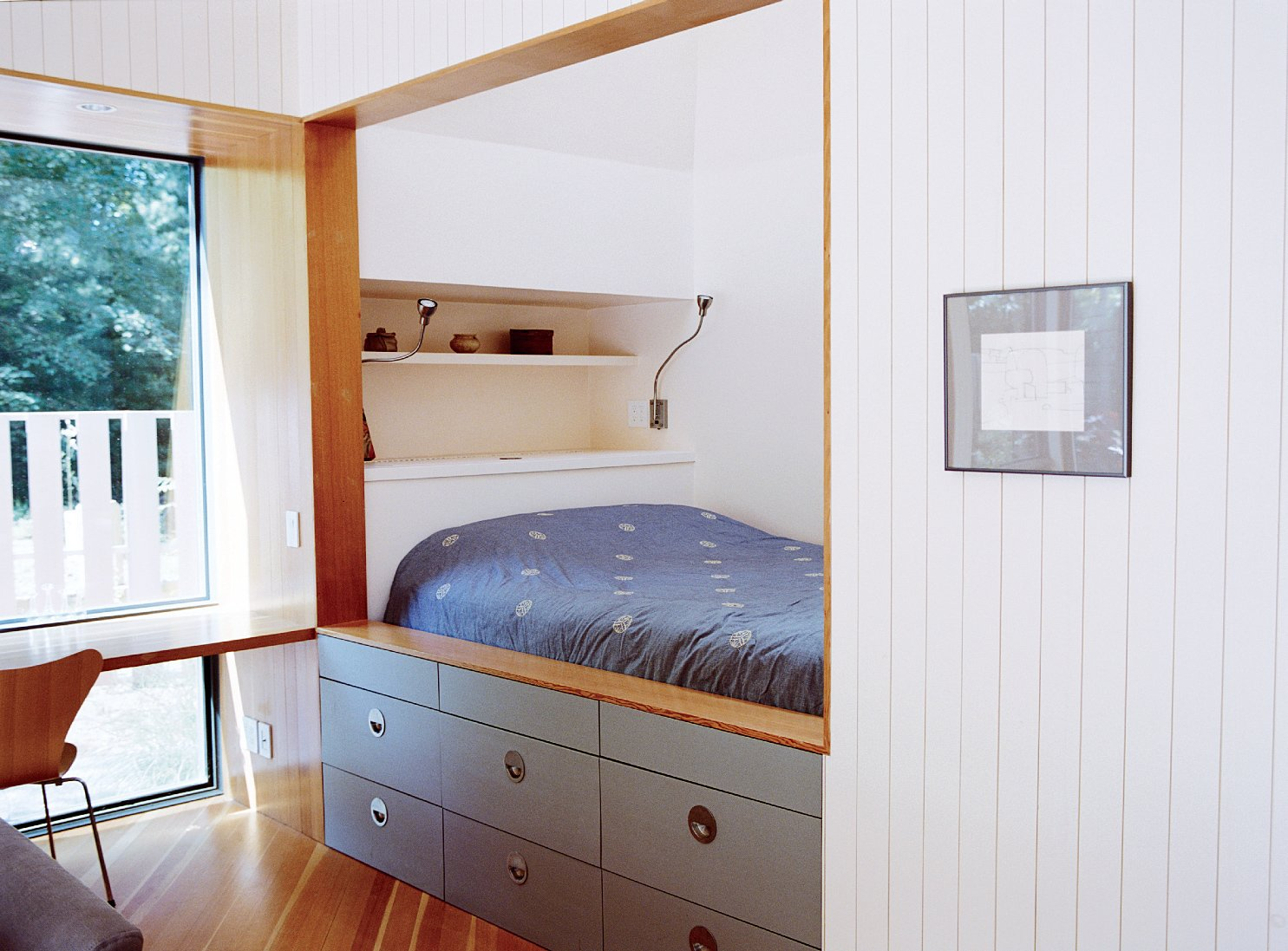 Key to the space-efficient floor plan is a strategically placed set of recessed areas, includingthe sleeping nook and writing desk. Tagged: Bedroom, Shelves, Medium Hardwood Floor, and Bed.  Photo 4 of 12 in This Tiny New England Cottage Is a No-Frills Weekend Hideaway