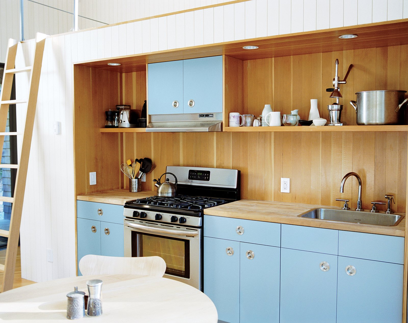 The kitchen area, which has IKEA cabinets with custom doors and pulls by Doug Mockett, is also recessed, with a lofted area above it. Tagged: Kitchen, Colorful Cabinet, and Wood Cabinet.  Photo 7 of 12 in This Tiny New England Cottage Is a No-Frills Weekend Hideaway