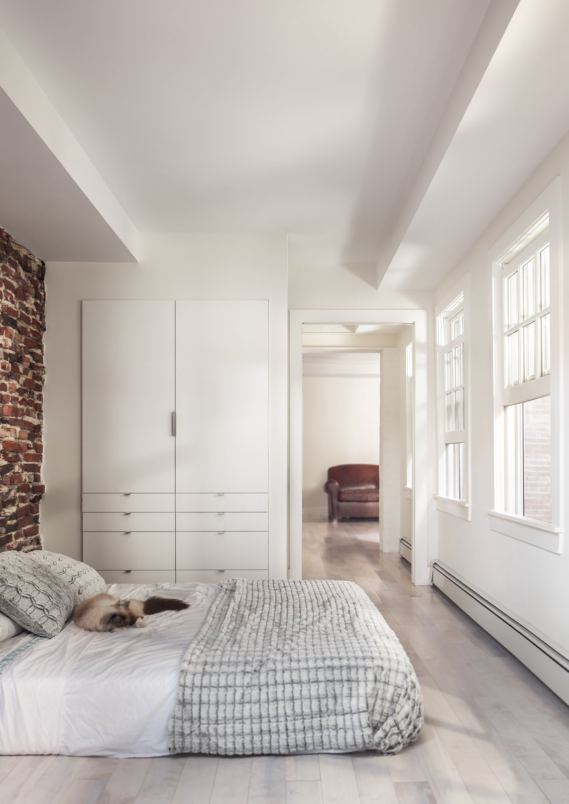 The renovation revealed a 30-foot-deep well beneath the bedroom, which the team half-jokingly considered turning into a fish tank. Instead, they opted for a simple bedroom with plenty of built-in storage. Tagged: Bedroom, Bed, and Light Hardwood Floor.  Bedrooms by Dwell from Beacon Hill