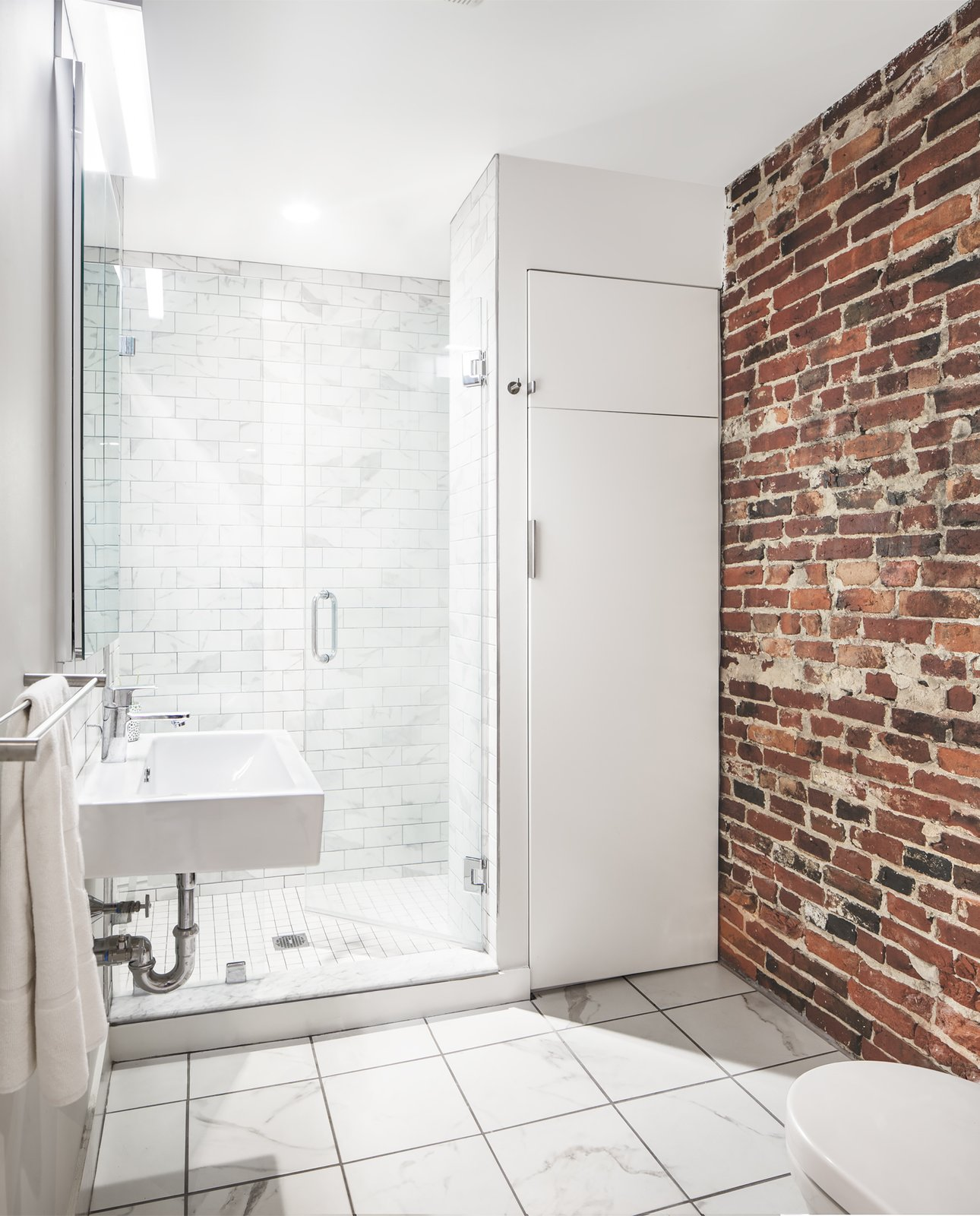 Along with historic wood and steel details, several warm brick walls were exhumed and left exposed. Tagged: Bath Room, Enclosed Shower, Porcelain Tile Floor, and Wall Mount Sink.  Bathroom by Solarwise from Beacon Hill