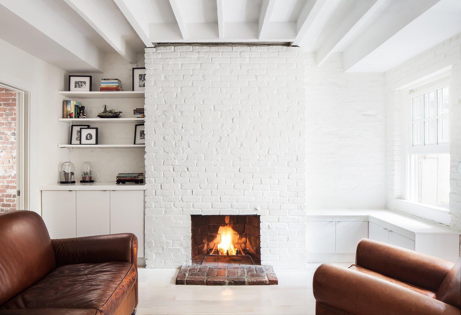 The historic apartment has been updated throughout with white paint and minimalist accents, adapting its rustic character to the 21st-century. Tagged: Living Room, Chair, Light Hardwood Floor, Wood Burning Fireplace, and Standard Layout Fireplace.  Photo 5 of 5 in An Archaeological Renovation Adds Precious Space to a Tiny Boston Apartment from Beacon Hill