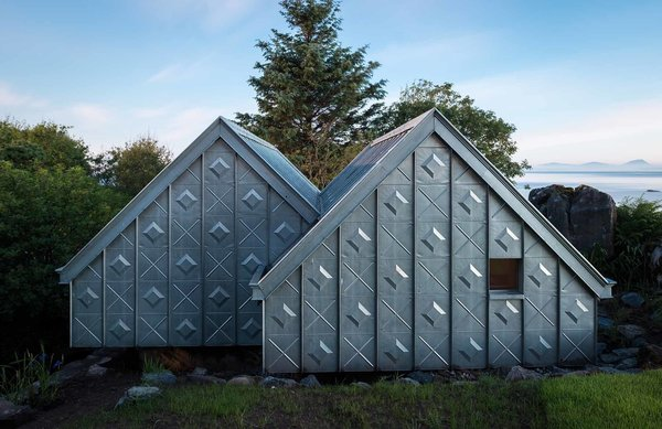"The studio is located in the natural context of the Scottish coast, with the island of Jura in the distance. A significant design challenge, according to Blake, was ""building something quite refined in an extreme and remote environment."" To overcome this logistical obstacle, much of the material was prefabricated offsite and transported to the building location. At the facade, elemental zinc is elevated from raw material to art piece by the unique cladding pattern. The custom embossed standing seam zinc system was designed in collaboration with VM Zinc, and fitted by HLMetals. Photo  of Midden Studio modern home"