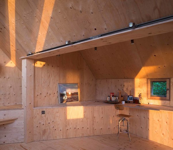 The studio's artist wanted a workspace that would be a blank canvas. Accordingly, sustainably sourced birch plywood was seamlessly used throughout the interior space. When it becomes weathered, damaged, or covered in paint, it can be easily removed and replaced. Photo 3 of Midden Studio modern home