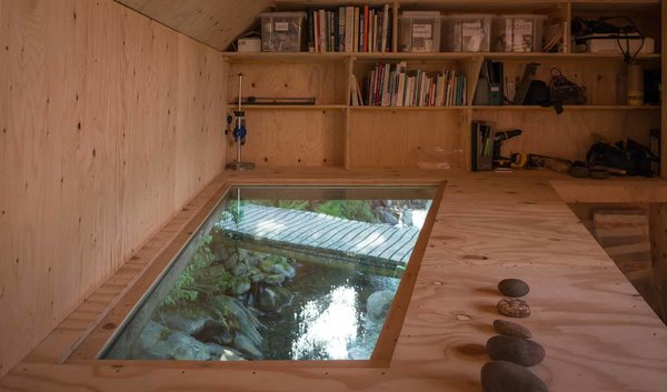 """A 'light soffit' offers a dynamic view of the stream below, providing both visual and audio stimulation. Throughout the year, the studio is filled with the sound of water, from the ocean waves to the rain and drizzle, to the flowing stream below. The artist, who has a longstanding connection to the site, focuses on """"art which leaves marks at once permanent and delicate,"""" much like the structure itself. Photo 6 of Midden Studio modern home"""