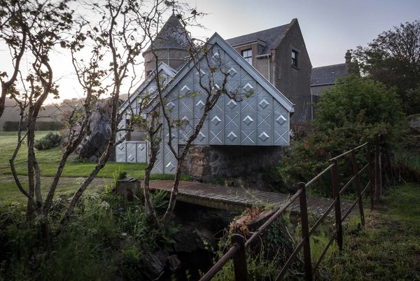 "While making its own unique mark, the studio is also deeply respectful towards its historic surroundings. The structure sits directly on top of a Victorian ""midden wall,"" an enclosure traditionally used by the adjacent stables as a depository for horse manure. The studio's twin gables mimic its direct neighbors, and the zinc molding on the gutter also echoes its Victorian predecessors. Photo 7 of Midden Studio modern home"