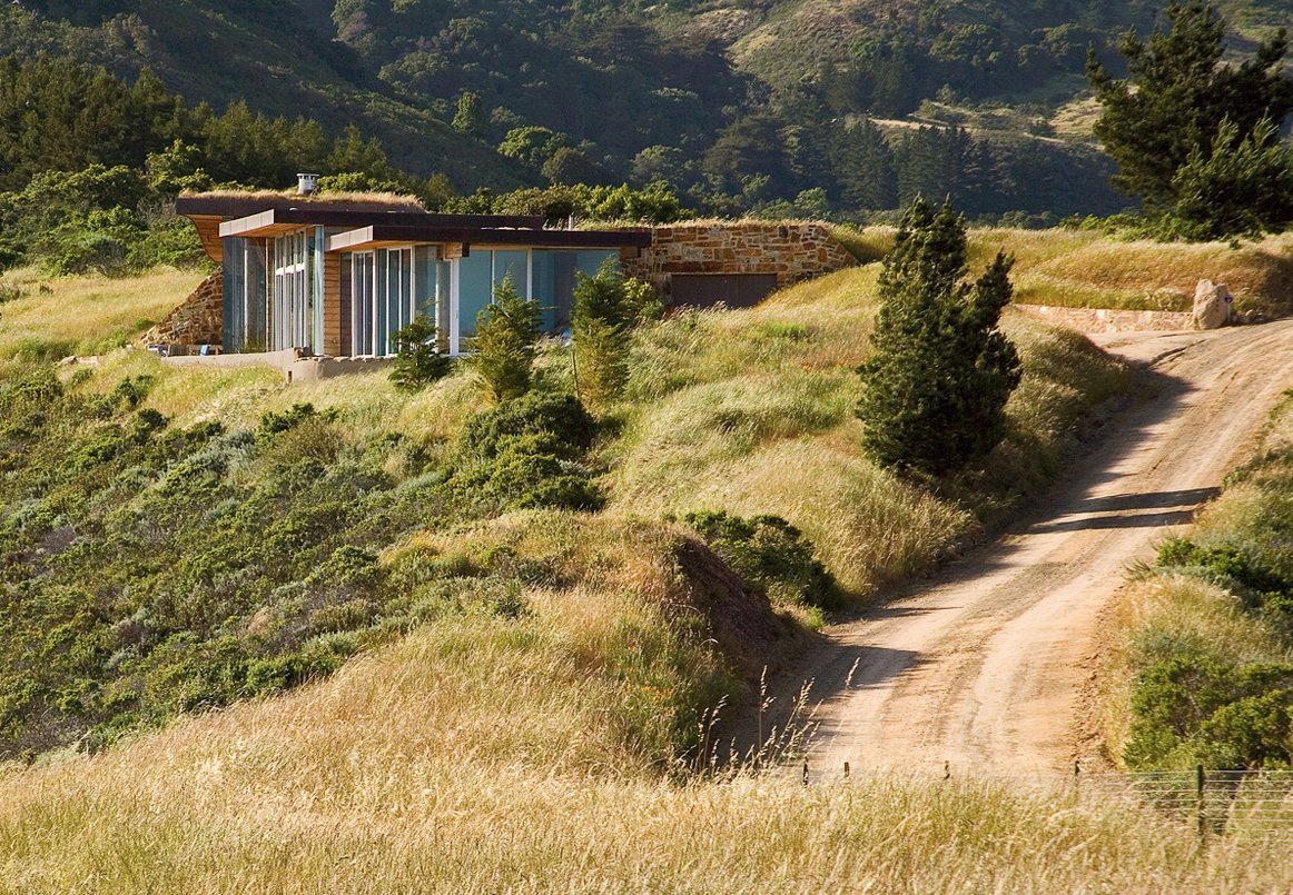 Native grasses, such as red fescue and California oat, dot the landscape surrounding this house in Big Sur.  Landscapes Designed with Native Plants by Zachary Edelson