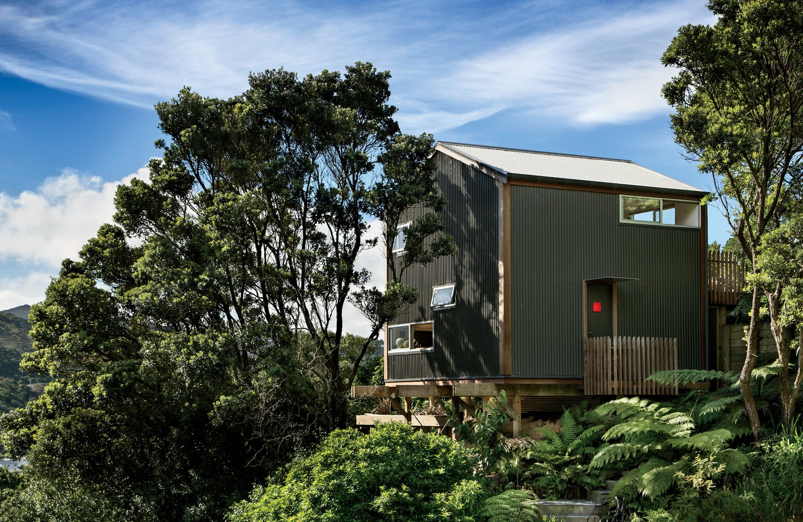 Inspired by the small scale of Japanese residences—in particular, Makoto Masuzawa's 1952 Minimum House—architect Andrew Simpson designed his own economical 538-square-foot home, set into a wooded site in Island Bay, a coastal suburb outside Wellington, New Zealand. Tagged: Exterior, House, Metal Siding Material, Gable RoofLine, and Metal Roof Material.  Small Spaces by Arthur Ohouo from A Home's High Ceilings Are Responsible for Some Impressive Views
