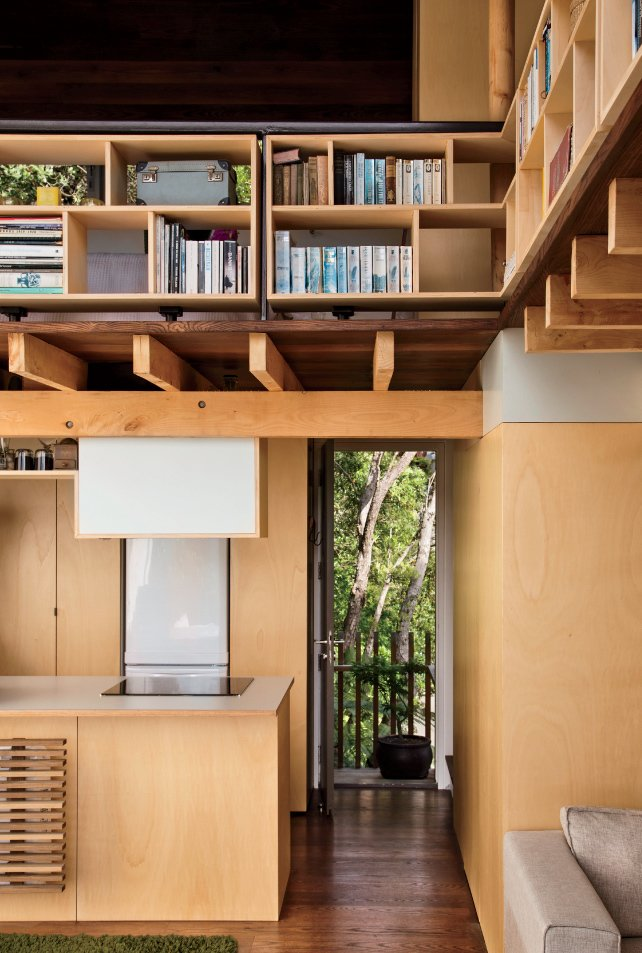 Architect and resident Andrew Simpson maximized the diminutive home with double-height ceilings, elevated compact shelving, and lofted sleeping quarters. Tagged: Storage Room and Shelves Storage Type.  Storage by Dwell from A Home's High Ceilings Are Responsible for Some Impressive Views