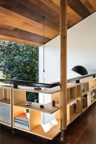 Simpson runs his practice, WireDog Architecture, from his home study, where custom bookshelves line the perimeter of the mezzanine for a storage solution that doubles as railing.