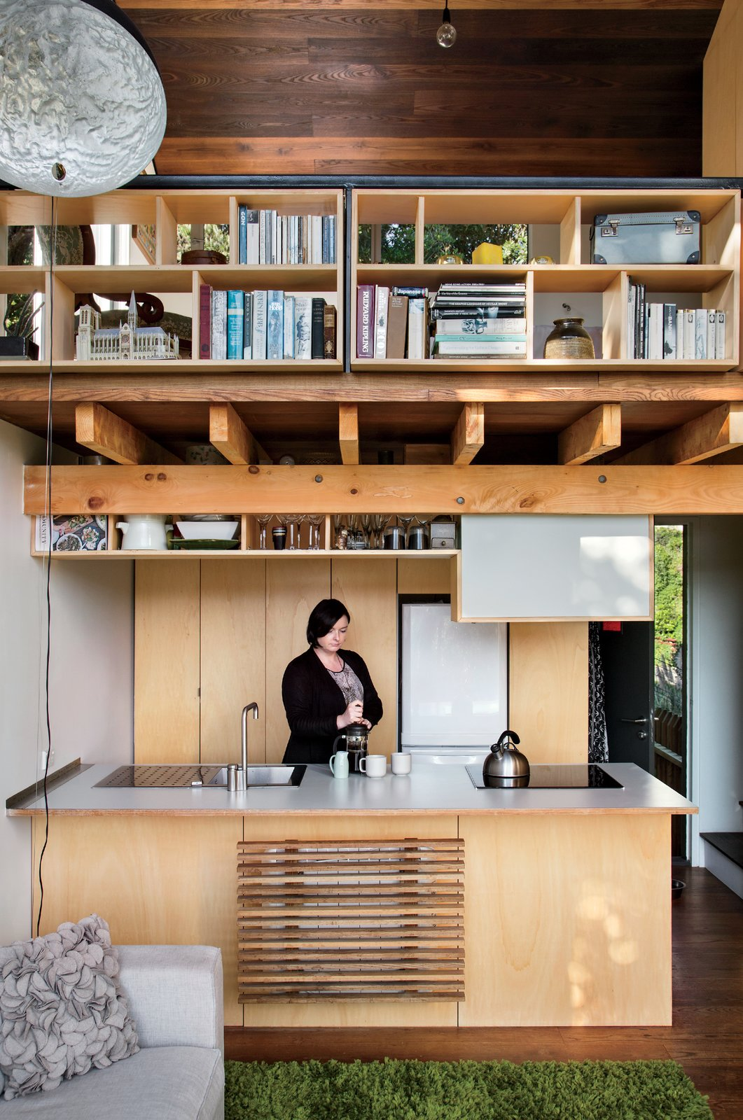 On the ground floor, Simpson's fiancée, Krysty Peebles, makes coffee in a compact kitchen outfitted with a Foraze Panni sink, Bosch induction cooktop, and Mitsubishi refrigerator.  Solutions For Tiny Kitchens by Aileen Kwun from A Home's High Ceilings Are Responsible for Some Impressive Views
