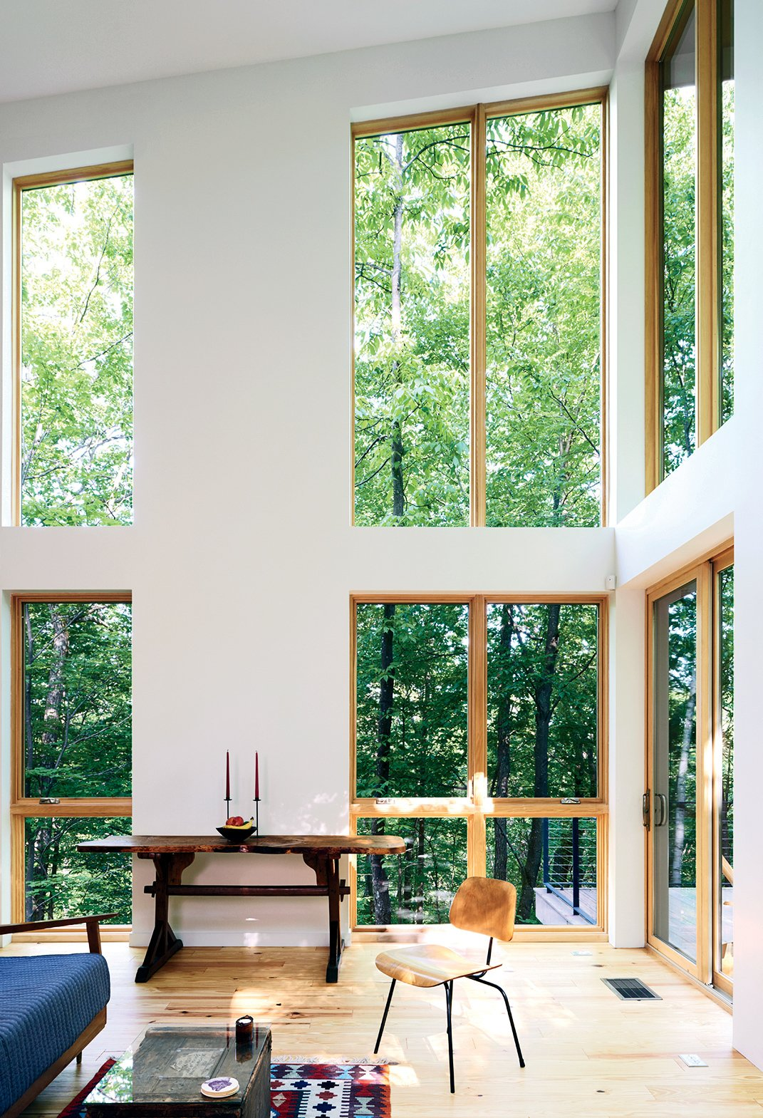 The residents splurged on double-height Marvin Integrity windows. Tagged: Living Room, Chair, and Light Hardwood Floor.  Photo 2 of 4 in A Little Cabin Cantilevered Over a Rocky Ledge in the Mountains