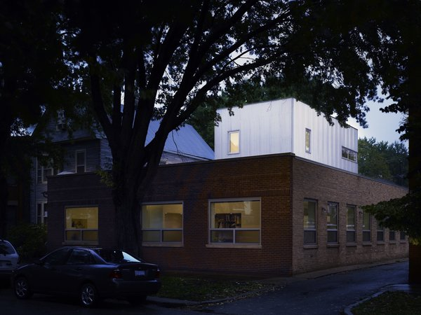 Appearing almost as a glowing container stack, the corrugated aluminum addition relates to the low-lying structure's commercial past. Not that owners Dave and Jeannette Jordano were saddled with rehab and remediation. The previous occupant, architecture firm Morgante Wilson, outgrew the 50-foot-by-50-foot footprint but left the space in fine condition.