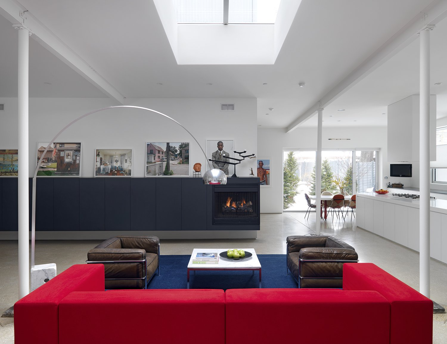 A new skylight regulates the living room's natural light. Ronan set up great contrasts in the space with the bone white walls and ceiling, black wall unit with built-in fireplace, and the crisply framed courtyard. The owners enhanced the space further with vibrant photography and furnishings. Tagged: Living, Chair, Sofa, Lamps, Recessed, Concrete, Standard Layout, Wood Burning, and Floor.  Best Living Wood Burning Recessed Photos from Ravenswood Residence