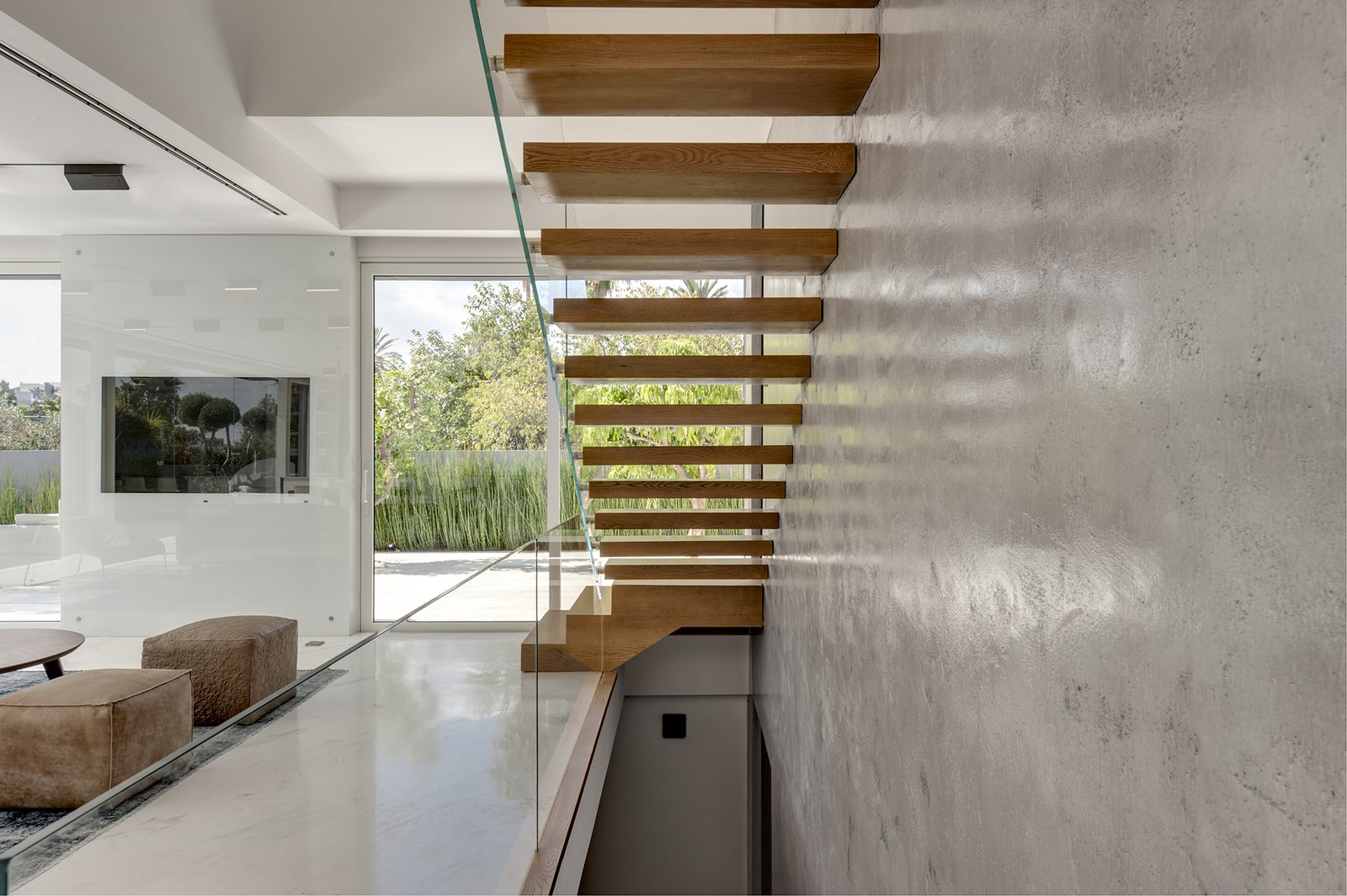 Inside, the home immediately opens up with light and natural views. The cantilevered stairs leading to the first floor offer a dramatic focal point. The stairs, wrapped in natural oak, are anchored to the exposed concrete walls on one side, and bordered by a clear glass railing on the opposite side.  Rishon Le Zion 3 by Sarah Akkoush