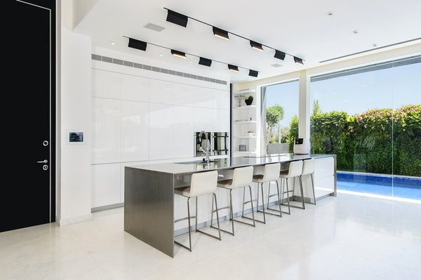 A well-lit and open ground floor with a strong interior-exterior connection was at the top of the family's wish list. The kitchen makes the most of a compact space through its intimate relationship with the adjacent pool and public outdoor space. The spaces features hardware-free white cabinets and a stainless steel center island. The white kitchen floors provide visual continuity with the white pavement directly outside. Photo 3 of Rishon Le Zion 3 modern home