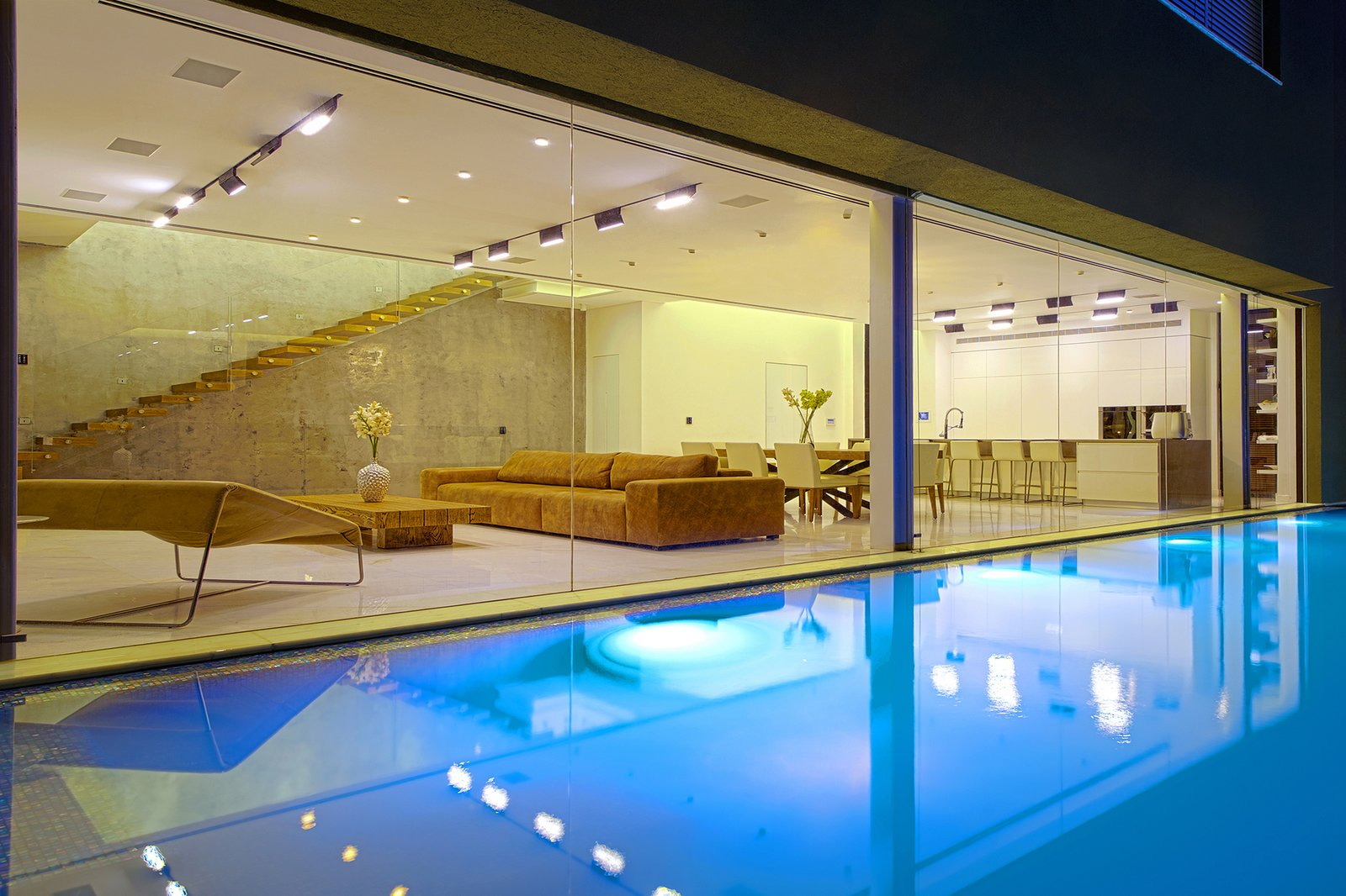 Along the side of the home, parallel to the pool, is an expansive glass wall that maximizes the feeling of openness in the first floor living space. The pool is heated by a repeated energy air-conditioning system, which conserves energy expenditure.  Rishon Le Zion 3 by Sarah Akkoush