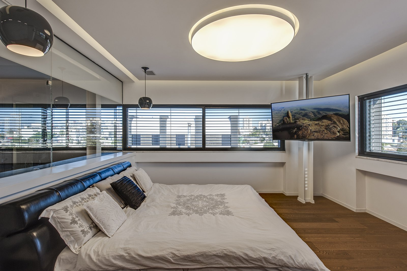 In the master bedroom, warm hardwood flooring and backlit perimeter lighting make the space bright and inviting. Panoramic windows overlook the urban cityscape, fostering a feeling of both openness and privacy.  Rishon Le Zion 3 by Sarah Akkoush