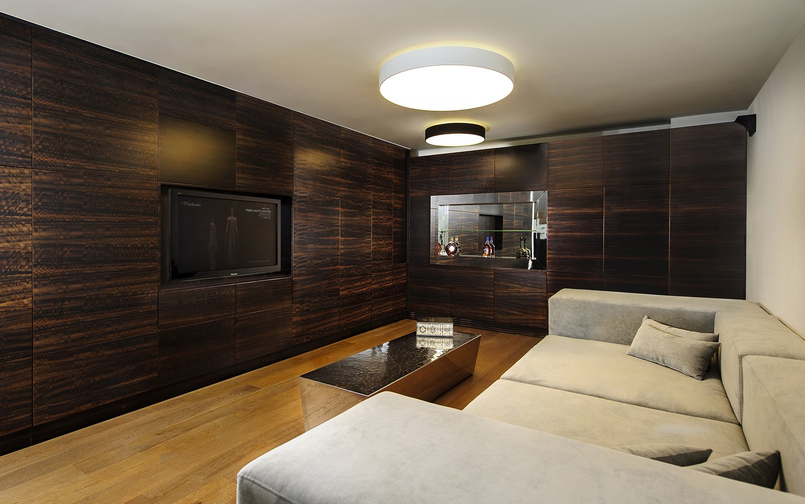 Downstairs in the basement, an entertainment room is inspired by the idea of an English pub. Dark, rich wood tones are favored in this popular meeting place for friends. The space was designed to be soundproof in order to maintain privacy from the two older children's bedrooms, also on the basement level. A wine bar, flat screen TV, and stainless steel table complete the space. Rishon Le Zion 3 by Sarah Akkoush