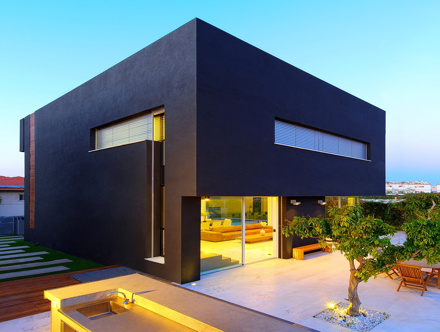 The voluminous black plaster cube appears to float over the open first-floor at the rear elevation. On the roof, solar panels generate about 80 percent of the home's electrical and heating needs. The landscaped backyard was designed to resemble an orchard, and includes several defined areas for socializing and entertaining.  Rishon Le Zion 3 by Sarah Akkoush