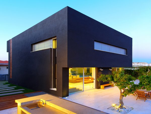 The voluminous black plaster cube appears to float over the open first-floor at the rear elevation. On the roof, solar panels generate about 80 percent of the home's electrical and heating needs. The landscaped backyard was designed to resemble an orchard, and includes several defined areas for socializing and entertaining. Photo 8 of Rishon Le Zion 3 modern home
