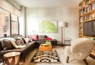 This Luxurious Apartment in Greenwich Village Is Only 520 Square Feet - Photo 3 of 6 - Along with a Dunbar sofa covered in Romo fabric, occasional seating includes a sheepskin Finn Juhl Pelican chair and a vintage wire chair. A BDDW coffee table sits atop a vintage rug. The artwork is by William Steiger.