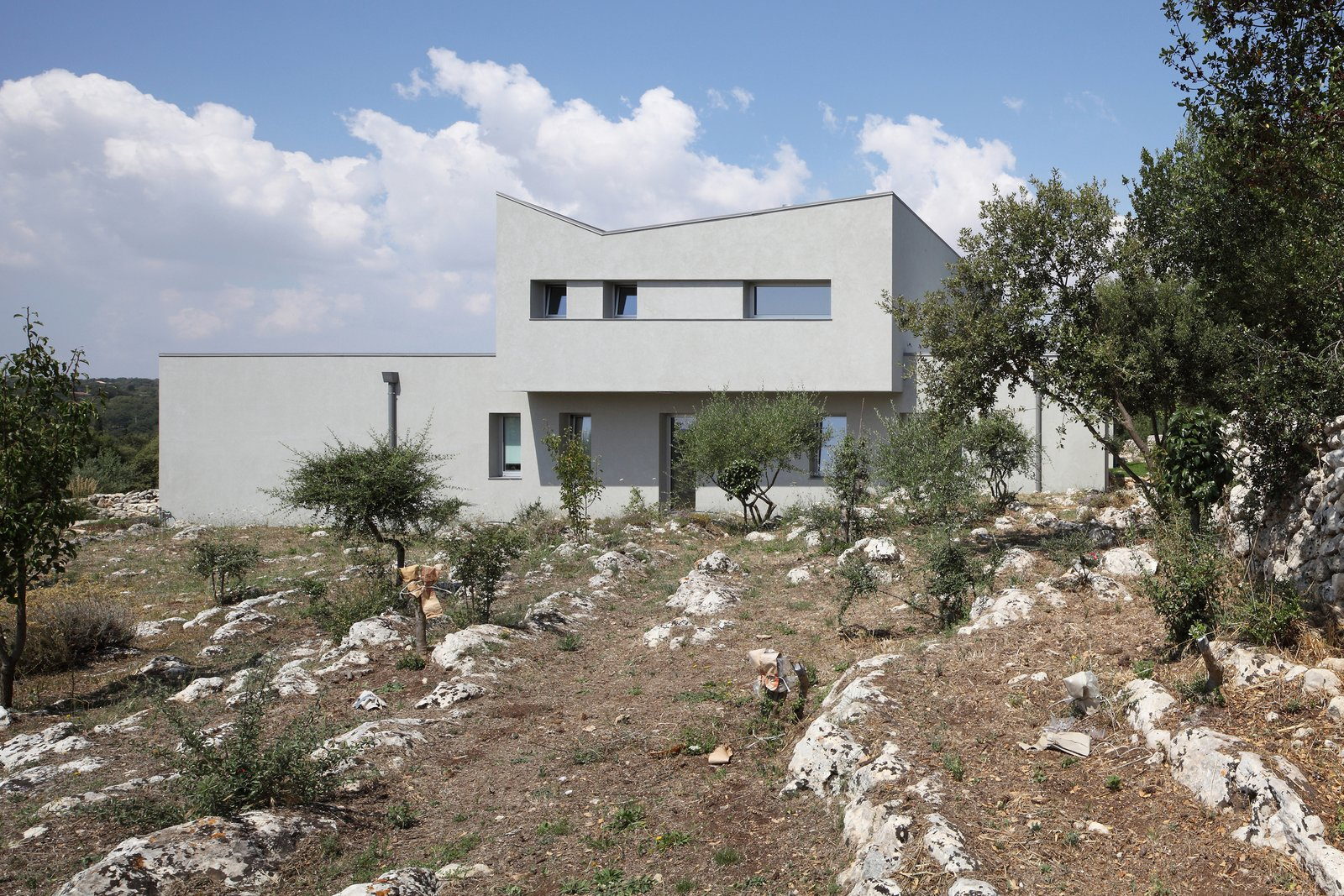 """A modern rendition of Mediterranean architecture combines with sparse landscaping to create a simple, minimalist feel. The climate, according to the architect, varies from """"the warmest African sunny days in summer [to] cold, rainy, and snowy days in winter."""""""