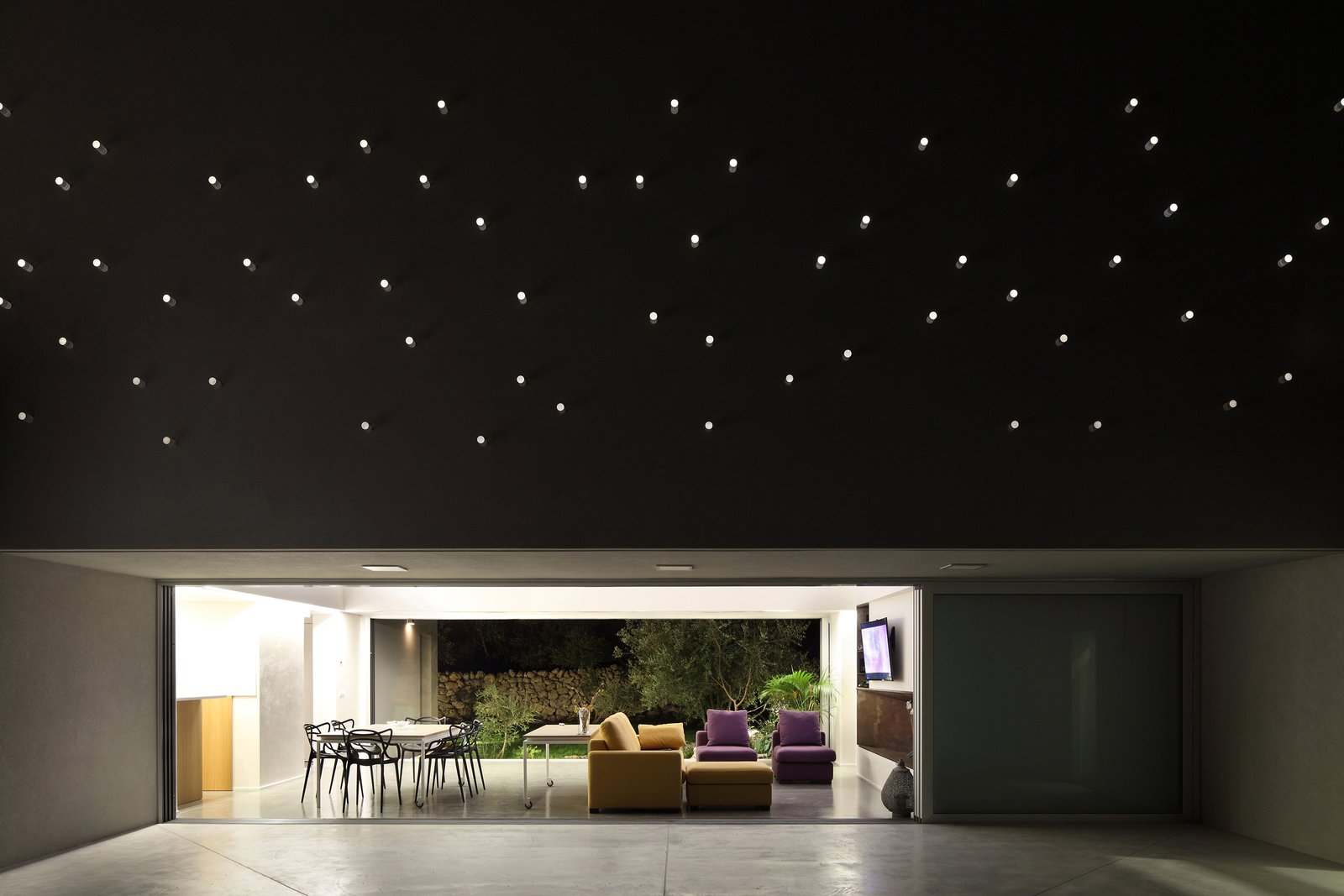 The plexiglass tube's reverse lighting scheme emulates a starry sky above the patio when the interior is lit up at night. Tagged: Exterior, House, and Concrete Siding Material.  A Home That Dramatically Replicates a Starry Sky in Its Living Room by Caroline Wallis