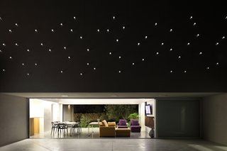 A Home That Dramatically Replicates a Starry Sky in Its Living Room - Photo 3 of 9 - The plexiglass tube's reverse lighting scheme emulates a starry sky above the patio when the interior is lit up at night.