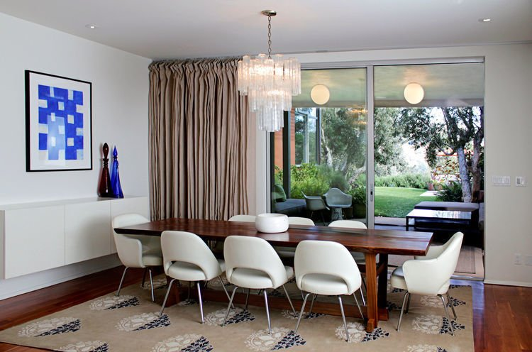 When midcentury enthusiast Margaret Riley bought an unispired ranch home in Los Angeles, she commissioned Cory Buckner to renovate it in the image of nearby architectural masterpieces. In the dining room, a glamorous 1970s chandelier hangs over a walnut table lined with Saarinen chairs.  47+ Midcentury Modern Homes Across America by Luke Hopping from Homes Featuring Luminous Chandeliers