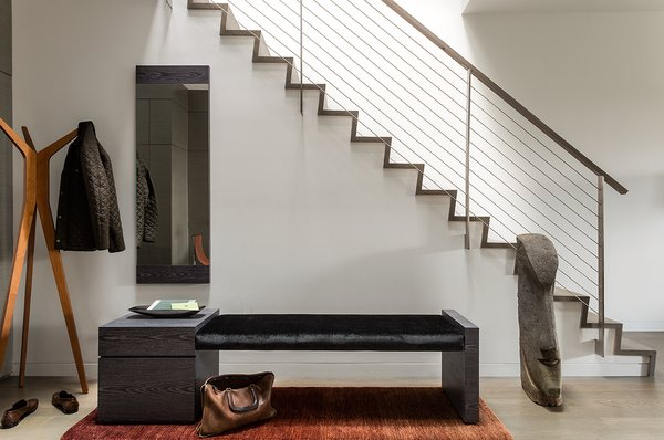 """The entire house is unified with oak flooring with a custom warm gray stain. This material is repeated on the stair and atrium handrails,"" Walker said. The entryway's bench has a custom Tabu Caleidolegno veneered wood base. The upholstered bench seat, which uses black Kravet fabric, was designed by Ruhl Walker Architects and made by Herrick & White. Photo 2 of Back Bay modern home"