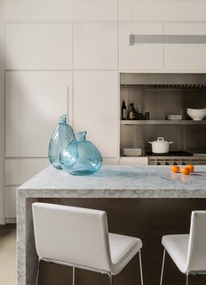 Mad About Marble: 20 Kitchens and Bathrooms - Photo 11 of 20 - Lineal Comfort stools upholstered in white leather by Andreu World sit across from turquoise glass vases from Neiman Marcus. Cumar supplied the white carrara marble for the island.