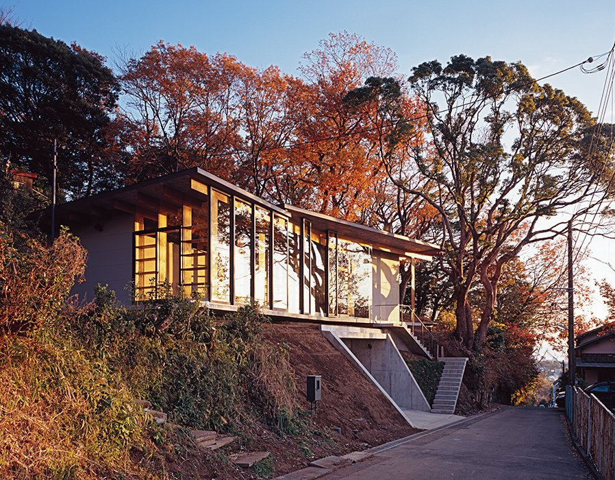 The architects designed the steel-frame doors and windows, which were fabricated by Takeuchi Kozai. Tagged: Exterior, House, Wood Siding Material, and Concrete Siding Material.  Photo 7 of 8 in Japanese Home Among the Trees Uses Bookshelves and Glass for Walls