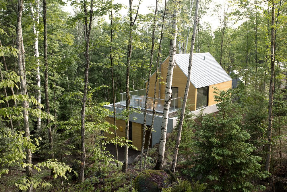 The facade consists of exposed concrete, Galvalume roofing, and cedar or torrefied wood coating. The homes are carefully positioned to keep other structures out of sight. Tagged: Exterior, Metal Roof Material, Wood Siding Material, House, and Cabin Building Type.  Photo 4 of 101 in 101 Best Modern Cabins from Spahaus
