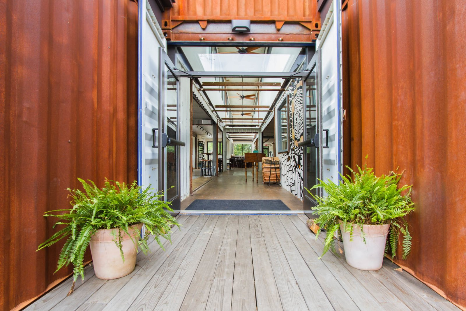 """""""We wanted it to feel open and spacious,"""" Alexander said. Much of the work on the containers was completed off-site by SG Blocks, and then delivered for construction. It's clad in Cor-Ten weathering seel.  A Restaurant Constructed from 19 Salvaged Shipping Containers by Kelly Dawson"""