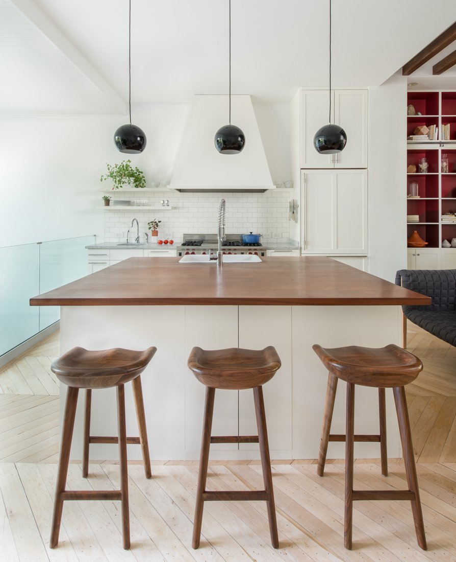 In the mostly-white kitchen, black Topan pendants by Verner Panton pop. The butcher block counters are an unusual height, so Lee designed custom-made stools to fit.  Color Splash by Kelsey Keith from Verner Panton Designs in Modern Homes