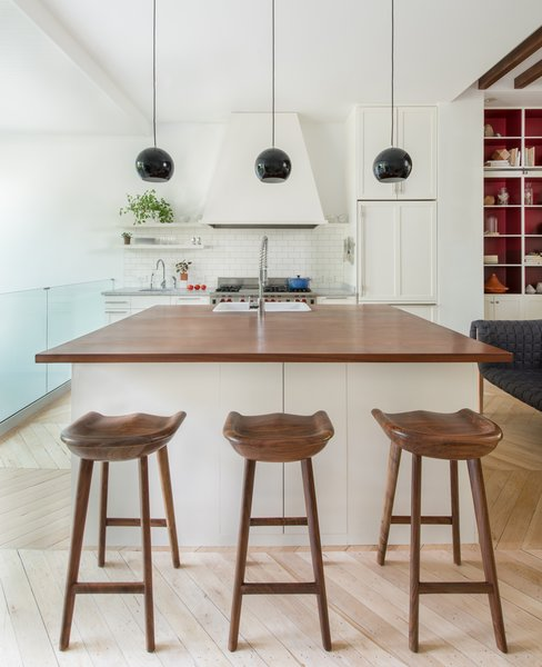 In the mostly-white kitchen, black Topan pendants by Verner Panton pop. The butcher block counters are an unusual height, so Lee designed custom-made stools to fit. Photo 3 of Color Splash modern home