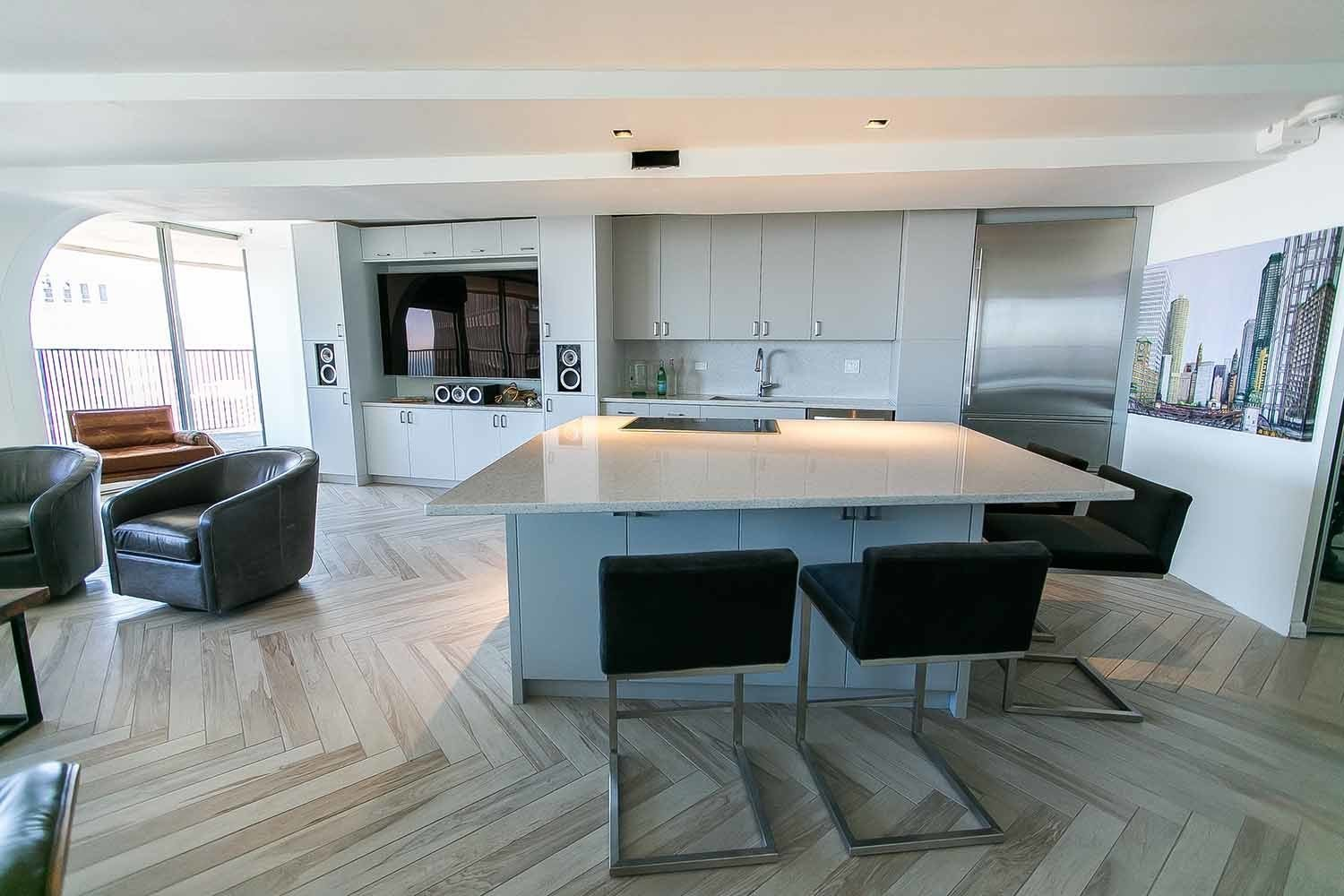 The all-new eat-in kitchen has an island with a Silestone quartz surface, comfortably seating six. To free up even more living space, an entertainment center is integrated into the back wall, adjacent to a seating nook.