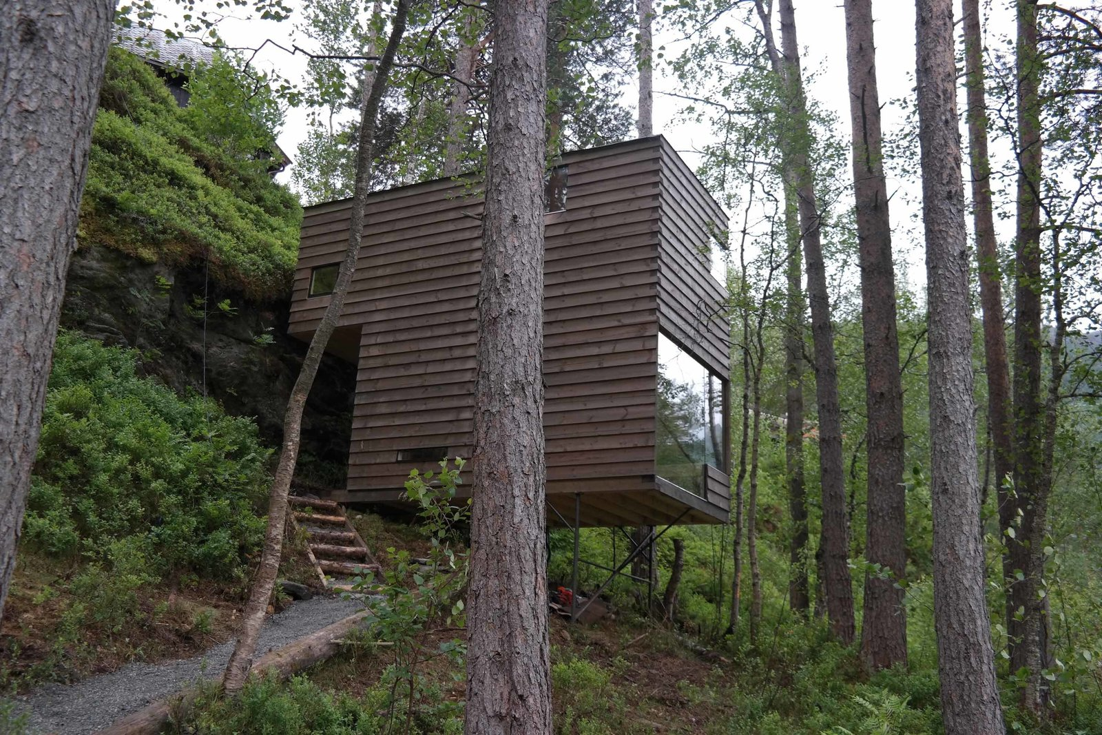 The two new cabins, also by Jensen & Skodvin Architects, are built on a steep hillside. They are held aloft by narrow steel rods and clad in a lumber stained to blend into the natural surroundings.