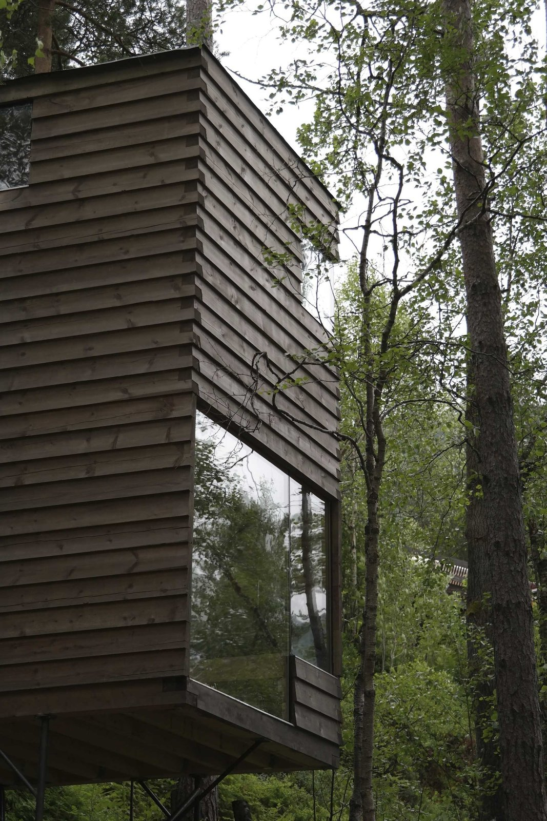 Windows are punctuate the façades of the new cabins at unexpected but strategic locations in order to frame and maximize views. Tagged: Exterior, Cabin Building Type, Wood Siding Material, Glass Siding Material, and Flat RoofLine.  Photo 5 of 8 in Rustic Cabins Comprise This Impossibly Idyllic Hotel in Norway