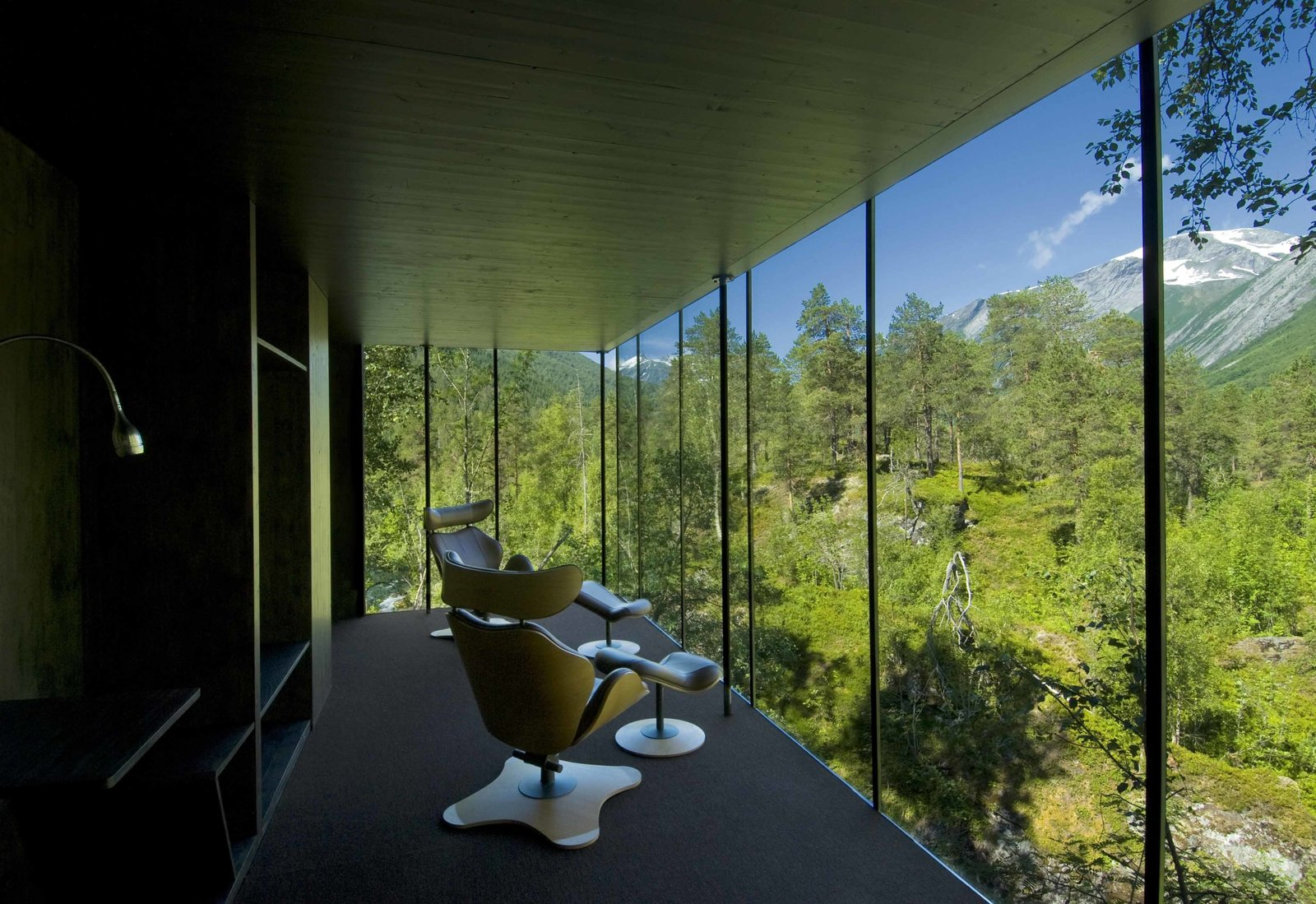 The walls of the original cabins are painted with black-pigmented oil to minimize reflections in the floor-to-ceiling windows—enhancing the sense of connection with the exterior scene.  Photo 7 of 8 in Rustic Cabins Comprise This Impossibly Idyllic Hotel in Norway