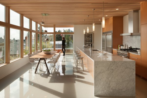 The ceiling on the main level of the home was built to reflect the same clear-stained cedar on the exterior. The mini pendants above the kitchen's waterfall island—which is made of Carrara marble—are by Minka Lavery. Photo 2 of Cedar Douglas Residence modern home