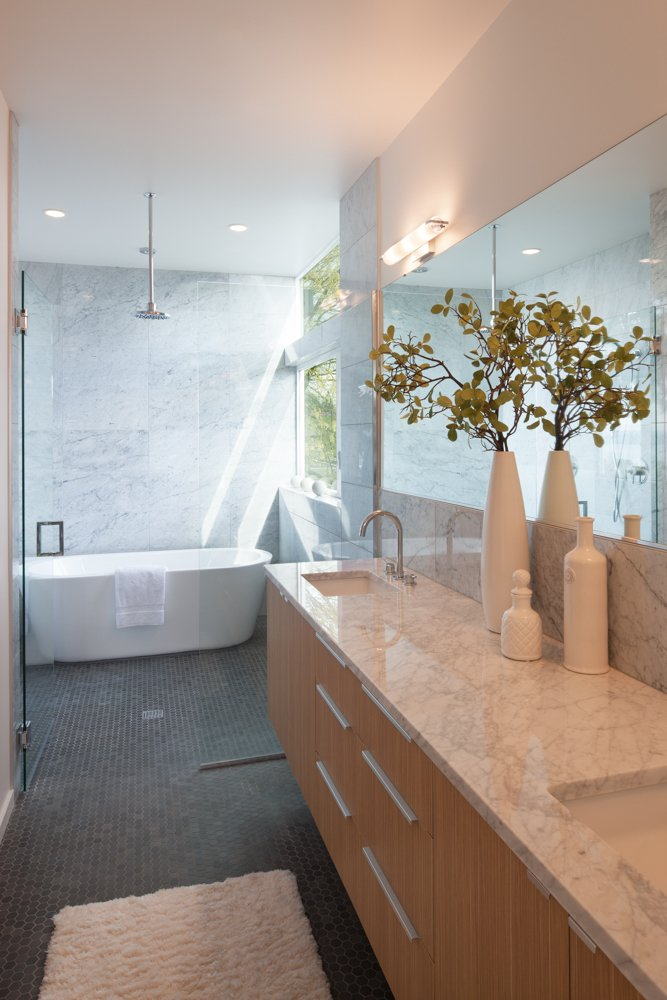 Edgewood cabinets adjoin countertops made from Carrara marble in the master bathroom. A Wyndham Collection bathtub sits under a chrome showerhead by Moen. Cedar Douglas Residence by Kelly Dawson
