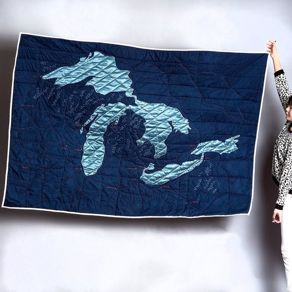 Another beautiful design from Haptic Lab and by Emily Fischer, the Great Lakes Quilt features light blue, poly-silk, hand-appliqued shapes against a navy background.