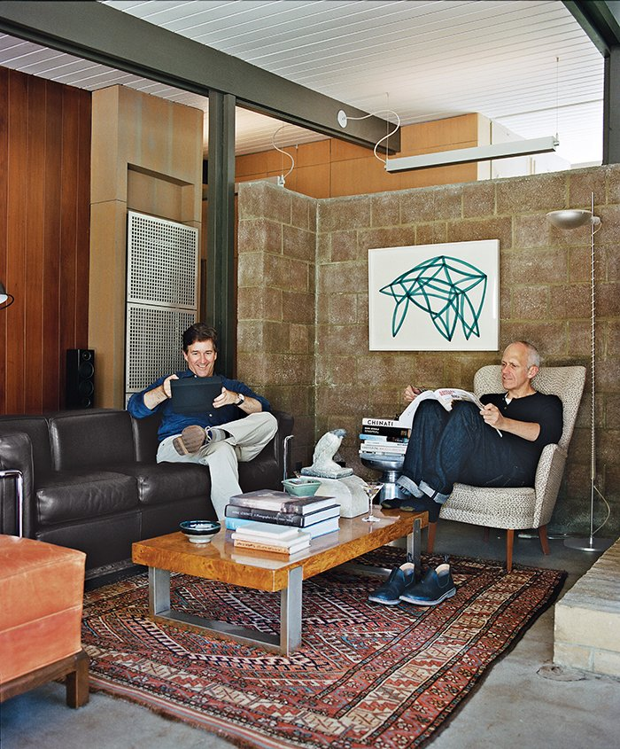 For their A. Quincy Jones house in Los Angeles, architect Bruce Norelius and his partner, Landis Green, retained and restored core elements, such as the living room's redwood paneling and concrete-block wall. Tagged: Living Room, Chair, Sofa, Rug Floor, and Concrete Floor.  Midcentury Homes by Dwell from L.A. Renovation Respects Midcentury Bones (While Adding Some Flair)