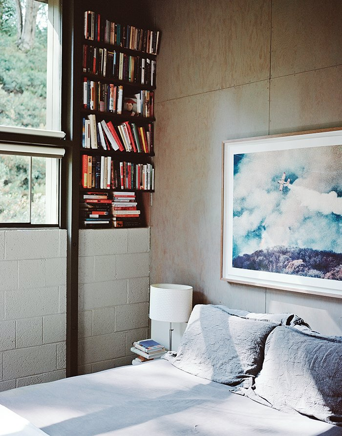 "In the master bedroom, above the Legnoletto by Alias bed, is a photograph by John Huggins. The lamp is from Ikea. ""Nothing is painted—all that stripping is about getting to the natural surfaces of the wood, and the concrete block,"" Norelius says. Tagged: Bedroom, Bed, Table Lighting, Shelves, and Bookcase.  Modern Bedroom Ideas  by Matthew Keeshin from L.A. Renovation Respects Midcentury Bones (While Adding Some Flair)"