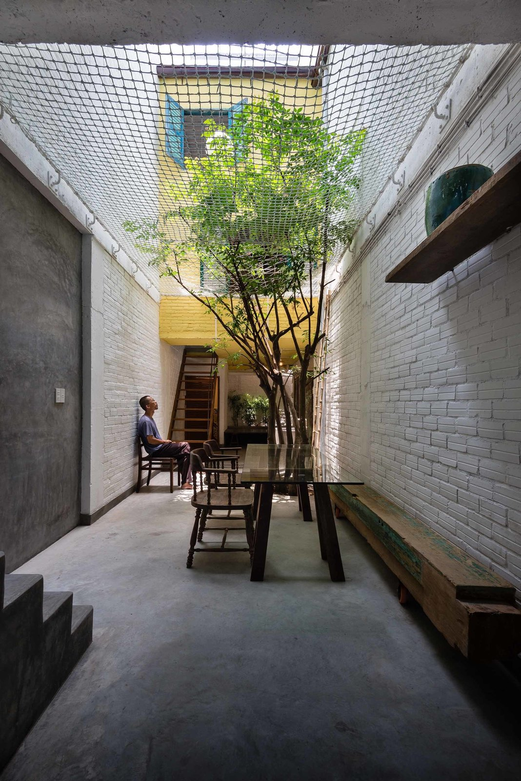 With so many small interior rooms and divisions between spaces, the addition of a net ceiling brings openness to the back alleyway, where the family often gathers to eat dinner. Not only does the net allow for ventilation and light, but it offers a place to play for the children, who love to climb and lounge above their parents.